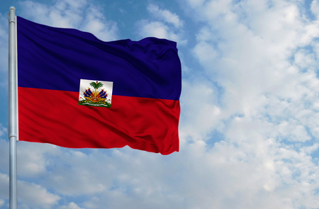 National flag of Haiti on a flagpole in front of blue sky.