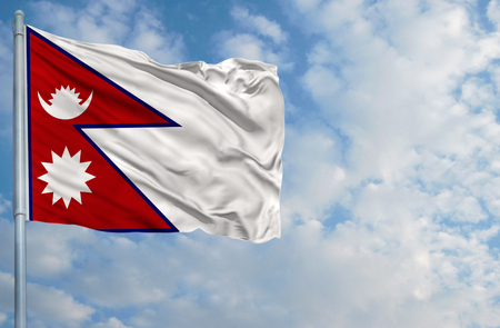 National flag of Nepal on a flagpole in front of blue sky. Stock Photo - 82118322