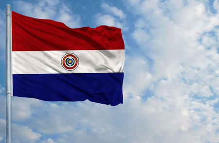 bandera de paraguay: National flag of Paraguay on a flagpole in front of blue sky.
