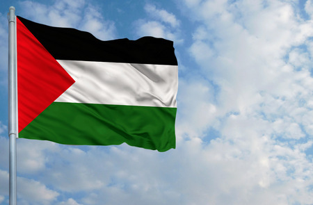 National flag of Palestine on a flagpole in front of blue sky.