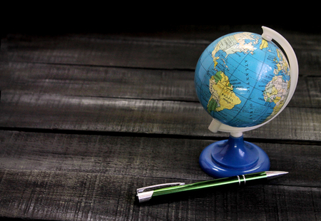 Globe with a pen on a wooden background with space for text.