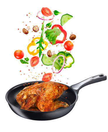 Frying pan with falling vegetables and chicken, isolated objects. Stock Photo