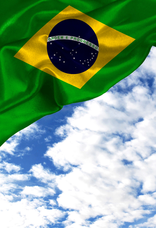 Grunge colorful flag Brazil, with copyspace for your text or images against a blue sky with clouds