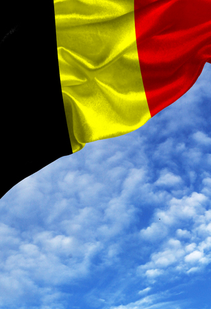 Grunge colorful flag Belgium, with copyspace for your text or images against a blue sky with clouds