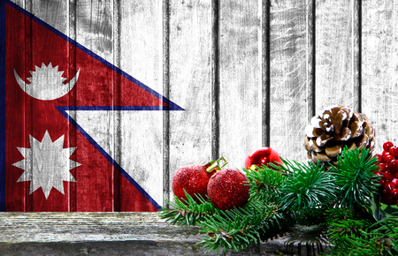 Wooden Christmas background with a flag of Nepal. There is a place for your text in the photo.