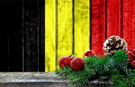 Wooden Christmas background with a flag of Belgium. There is a place for your text in the photo. Stock Photo