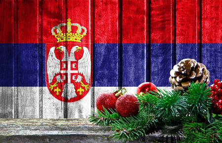 Wooden Christmas background with a flag of Serbia. There is a place for your text in the photo.