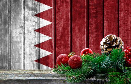 Wooden Christmas background with a flag of Bahrain. There is a place for your text in the photo.