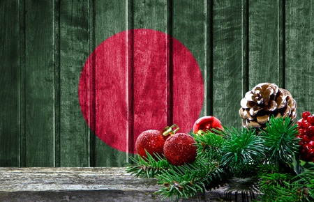 Wooden Christmas background with a flag of Bangladesh. There is a place for your text in the photo.