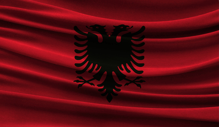 Realistic flag of Albania on the wavy surface of fabric. This flag can be used in design