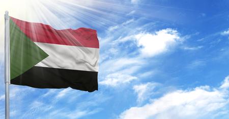 Flag of Sudan on flagpole against the blue sky.