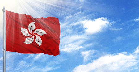 Flag of Hong Kong on flagpole against the blue sky.