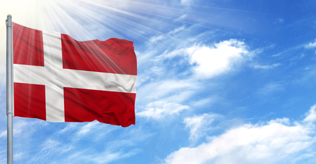 Flag of Denmark on flagpole against the blue sky.
