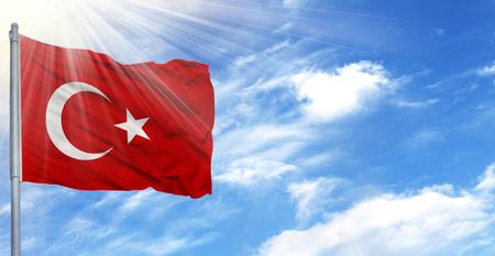 Flag of Turkey on flagpole against the blue sky.