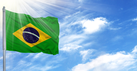 Flag of Brazil on flagpole against the blue sky.