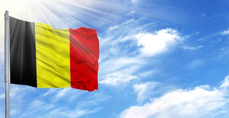 Flag of Belgium on flagpole against the blue sky. Stock Photo