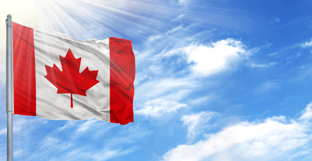 Flag of Canada on flagpole against the blue sky.