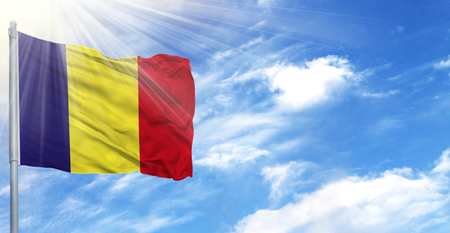 Flag of Romania on flagpole against the blue sky.