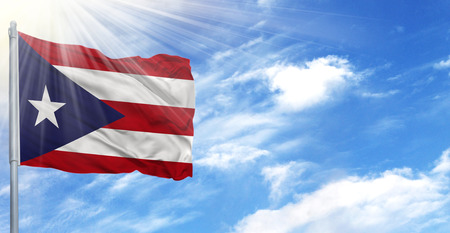 Flag of Puerto Rico on flagpole against the blue sky. Stock Photo