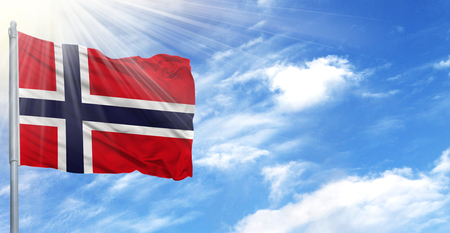 Flag of Norway on flagpole against the blue sky.