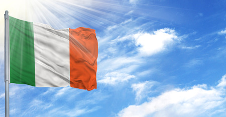 Flag of Ireland on flagpole against the blue sky.