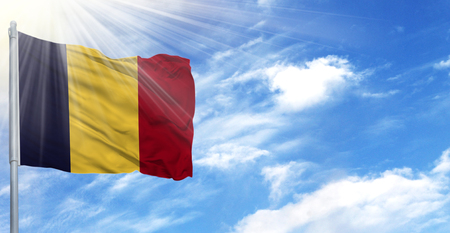 Flag of Chad on flagpole against the blue sky.