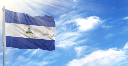 Flag of Nicaragua on flagpole against the blue sky. Banco de Imagens