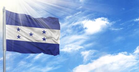 Flag of Honduras on flagpole against the blue sky.