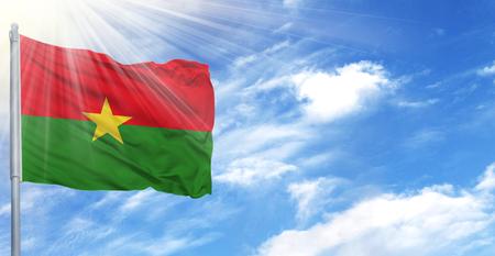Flag of Burkina Faso on flagpole against the blue sky.