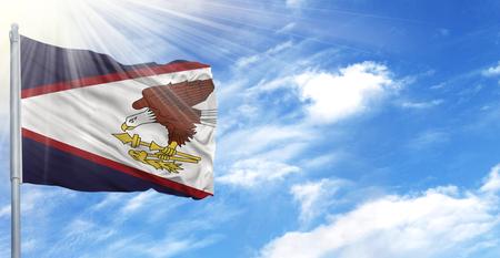 Flag of American Samoa on flagpole against the blue sky.