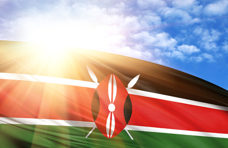 flag of Kenya against the blue sky with sun rays.