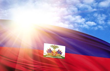 flag of Haiti against the blue sky with sun rays.