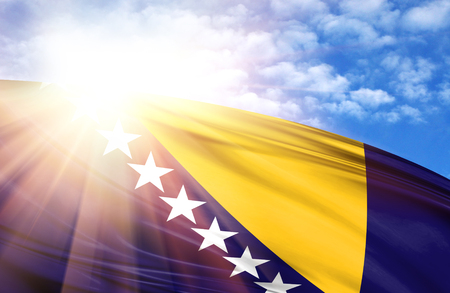 flag of Bosnia and Herzegovina against the blue sky with sun rays. Stock Photo