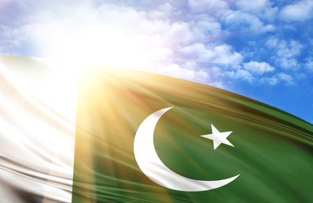 flag of Pakistan against the blue sky with sun rays.