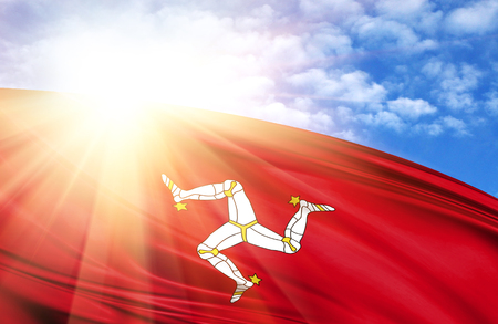 flag of Isle Of Man against the blue sky with sun rays.