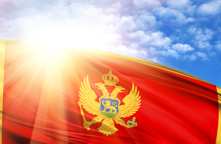 flag of Montenegro against the blue sky with sun rays. Stock Photo