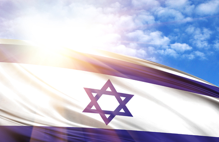 flag of Israel against the blue sky with sun rays.