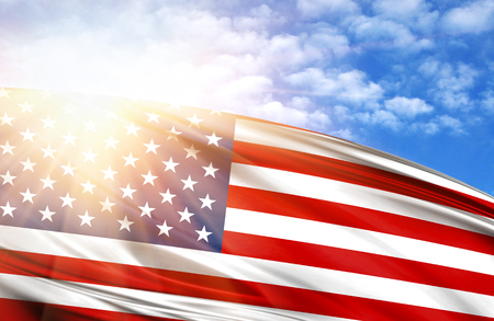 flag of America against the blue sky with sun rays.