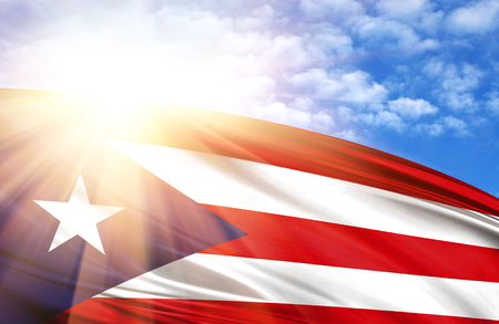 flag of Puerto Rico against the blue sky with sun rays. Stock Photo