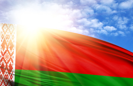 flag of Belarus against the blue sky with sun rays. Stock Photo