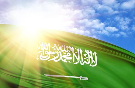 flag of Saudi Arabia against the blue sky with sun rays.