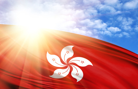flag of Hong Kong against the blue sky with sun rays. Stock Photo