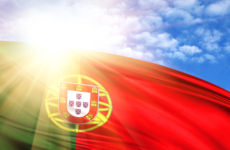 flag of Portugal against the blue sky with sun rays.