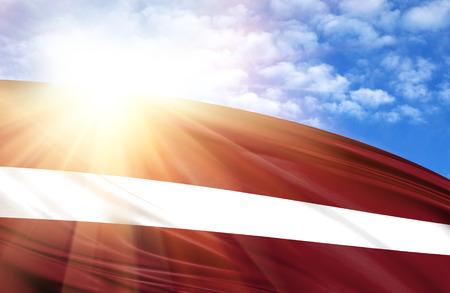 Flagge Lettlands gegen den blauen Himmel mit Sonnenstrahlen.