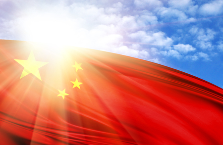 flag of China against the blue sky with sun rays.