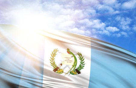 flag of Guatemala against the blue sky with sun rays. Stock Photo