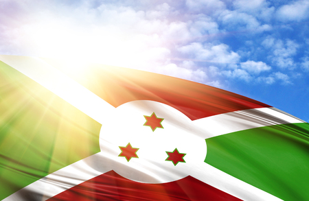 flag of Burundi against the blue sky with sun rays. Stock Photo