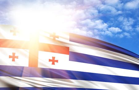 flag of Adjara against the blue sky with sun rays. Stock Photo