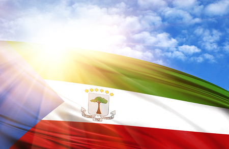 flag of Equatorial Guinea against the blue sky with sun rays.