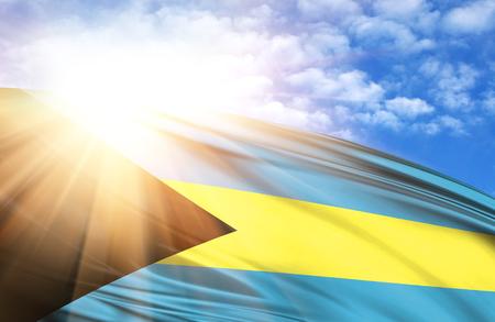 flag of Bahamas against the blue sky with sun rays. Stock Photo